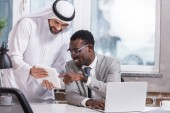Fotografie Multicultural businessmen using digital tablet in modern office