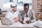 Multikulturní podnikatelé při pohledu na digitální tabletu v moderní kanceláři