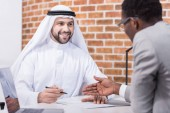 Arabian businessman signing contract at office desk