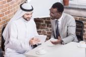 Arabian businessman holding digital tablet and sitting near african american partner