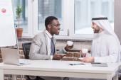 Mnohonárodnostní obchodníci sedí a pití kávy v kanceláři