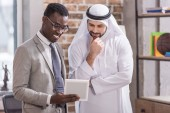 Arabian businessman looking at digital tablet and thinking near african american partner