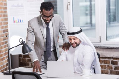 Multicultural businessmen looking at computer in modern office