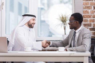 Multicultural businessmen shaking hands in modern office