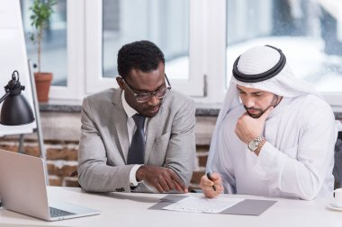 Multicultural businessmen looking at contract at office desk