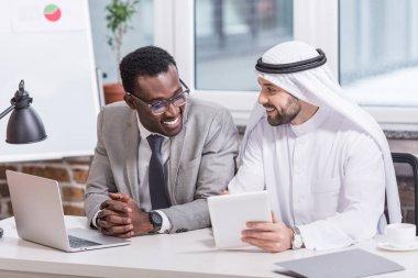 Multiethnic business partners using digital device in modern office