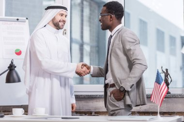 Cheerful businessmen shaking hands and smiling in office