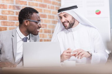 Arabian businessman looking at african american partner and smiling in office