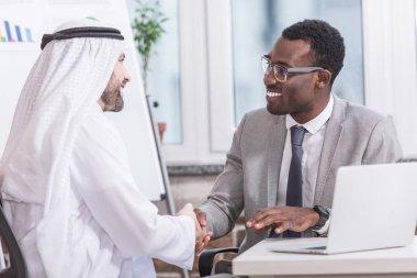 Smiling multicultural businessmen shaking hands in modern office