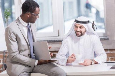 Arabian businessman looking at laptop in office