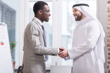 Multicultural businessmen smiling and shaking hands in modern office