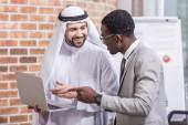 Fotografie Multicultural businessmen pointing at laptop in modern office