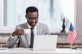 Fotografie African american businessman drinking coffee and using laptop
