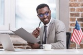 Fotografie African american businessman holding folder and pen in office