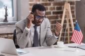 Fotografie African american businessman talking on smartphone in office