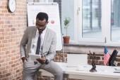 Afro-amerikai üzletember nézett digitális tabletta, a kéz a zsebben