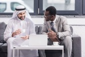 African american businessman looking at arabian partner and smiling in office