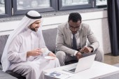 Fotografie Multicultural businessmen sitting and looking at laptop in modern office