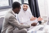 Fotografie smiling arabian businessman and african american partner talking in office