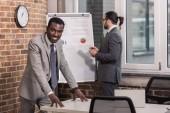 afro-amerikai üzletember keresi a kamera és a partner előtt álló flip-chart