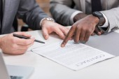cropped view of multiethnic business partners signing contract on office table