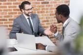 Multiethnische Geschäftsleute lächeln und unterhalten sich am Tisch mit Laptop
