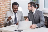 Fotografie handsome businessman pointing at laptop and smiling african american partner drinking coffee in modern office