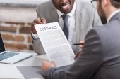 cropped view of african american businessman showing contract to partner
