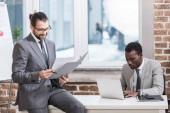 schöner Geschäftsmann sitzt am Tisch und liest Dokument, während afrikanischer amerikanischer Partner im Büro auf Laptop-Tastatur tippt