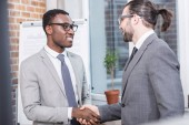 Fotografie smiling multiethnic businessmen shaking hands in office