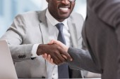 Photo cropped view of multiethnic businessmen in suits shaking hands