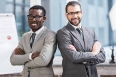 close up view of two multiethnic businessmen with arms crossed in office