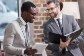 Erfolgreiche multikulturelle Geschäftsleute mit digitalem Tablet und Mappe diskutieren im Büro