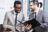 Fotografie successful multiethnic businessmen with digital tablet and folder smiling in office