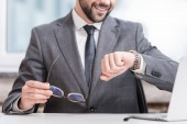 Photo cropped view of smiling businessman holding glasses and looking at watch
