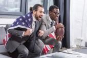 hezký mnohonárodnostní muži v oblecích s americkou vlajkou na bedrech sledovat americký fotbalový zápas v úřadu