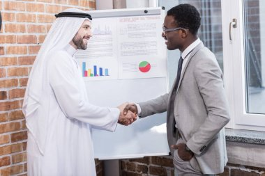 Multiethnic businessmen shaking hands near white board in office