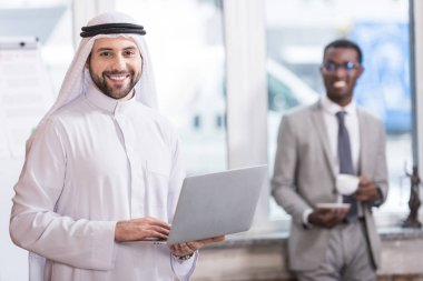 Arabian businessman holding laptop in office with african american partner on background
