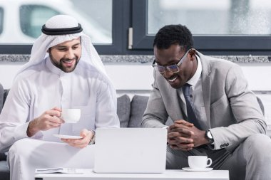 Businessmen looking on laptop and smiling in modern office