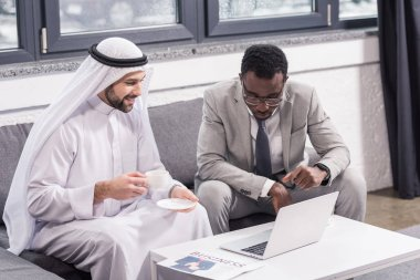 Multicultural businessmen sitting and looking at laptop in modern office