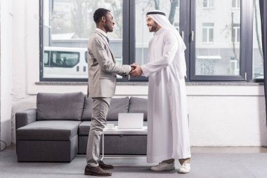african american businessman and arabic business partner standing and shaking hands in office