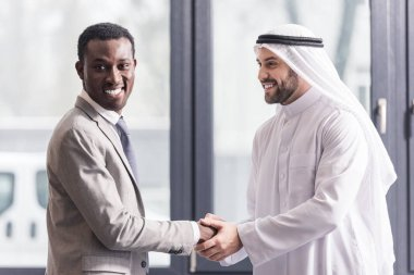close up view of african american businessman and arabic partner shaking hands in office