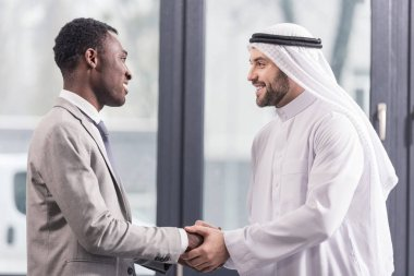 close up view of african american businessman and arabic partner smiling and shaking hands in office