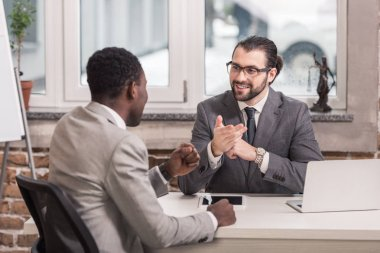 successful multicultural businessmen sitting at table and having discussion in office