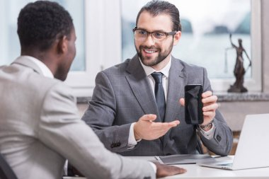 smiling businessman showing smartphone screen to african american partner in office