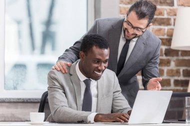african american businessman typing on laptop keyboard while smiling partner talking to him