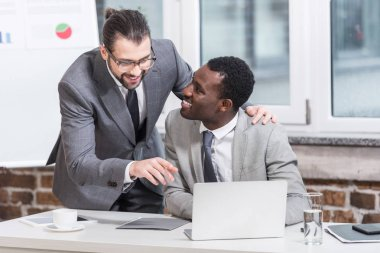 handsome businessman embracing african american partner and pointing at laptop in office