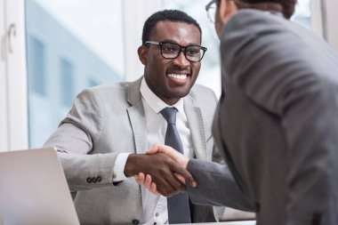 Close up view of smiling multiethnic businessmen shaking hands in office stock vector