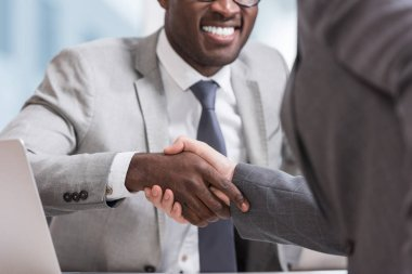 cropped view of multiethnic businessmen in suits shaking hands