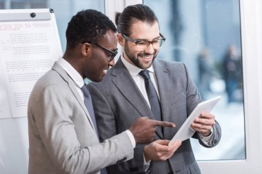 multiethnic business partners looking at digital tablet in office